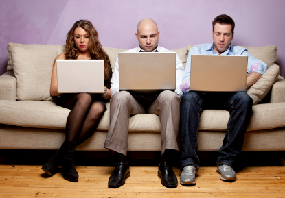 Three people using laptops while seated closely on a couch
