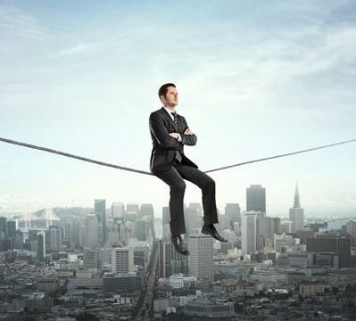 man in business suit sitting on wire high above city