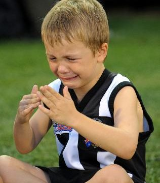 kid wearing Collingwood jersey crying