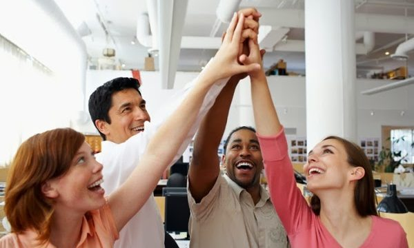 four team members holding up hands for group high five