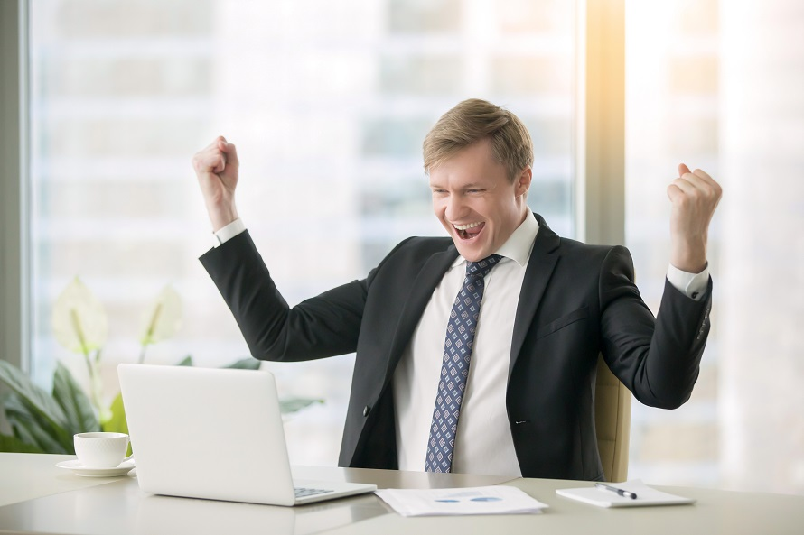 Businessman cheering and smiling while looking at a laptop screen