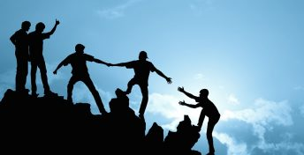 Silhouette of a group of people helping each other climb a mountain, arms outreached