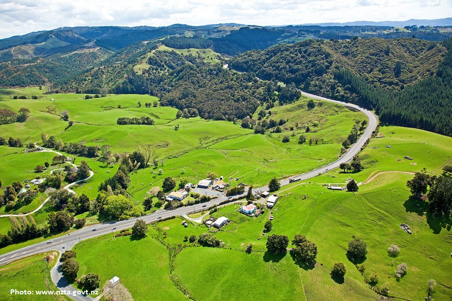 Puhoi aerial view - lush green fields and forest with a small group of buildings