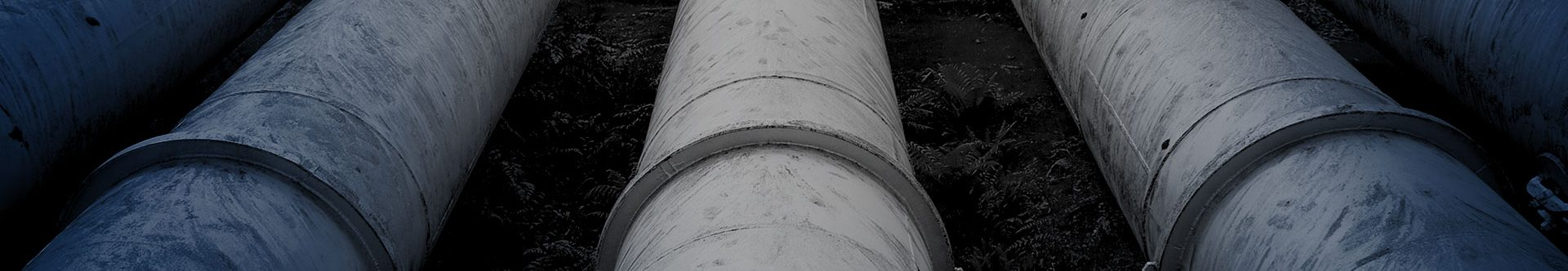 Large industrial pipes laid in a row, black and white image