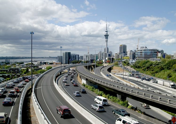 Late afternoon traffic in Auckland, New Zealand; downtown skyline with Sky-Tower in the background
