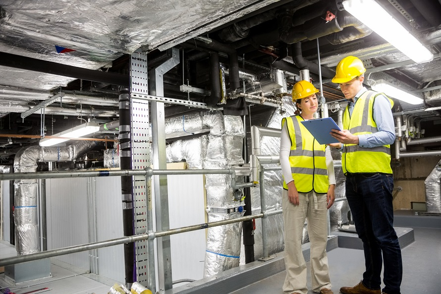 Two industrial workers completing a service review of an industrial interior area
