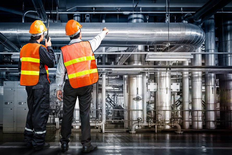 Industrial workers reviewing an industrial interior area