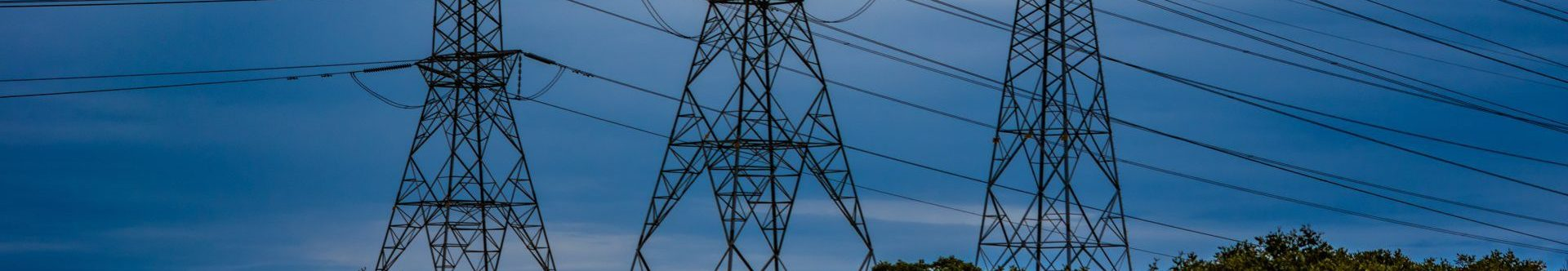 Electrical towers and power lines over trees and a blue sky